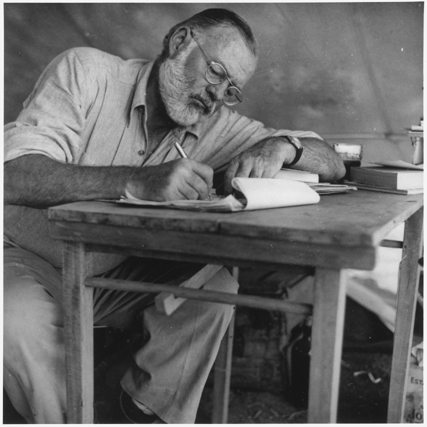 ernest_hemingway_writing_at_campsite_in_kenya_-_nara_-_192655